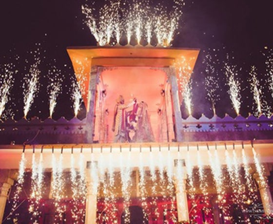 Garland ceremony on the terrace of Fatehgarh, Udaipur with traditional fireworks to make your wedding moments in Rajasthan spectacular
